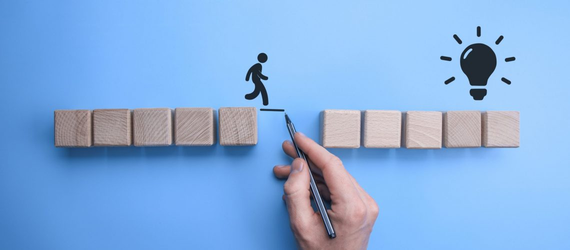 Male bussinnes man hand drawing a connecting line between two sets of wooden blocks for a silhouetted man to walk across.Conceptual of teamwork and support.
