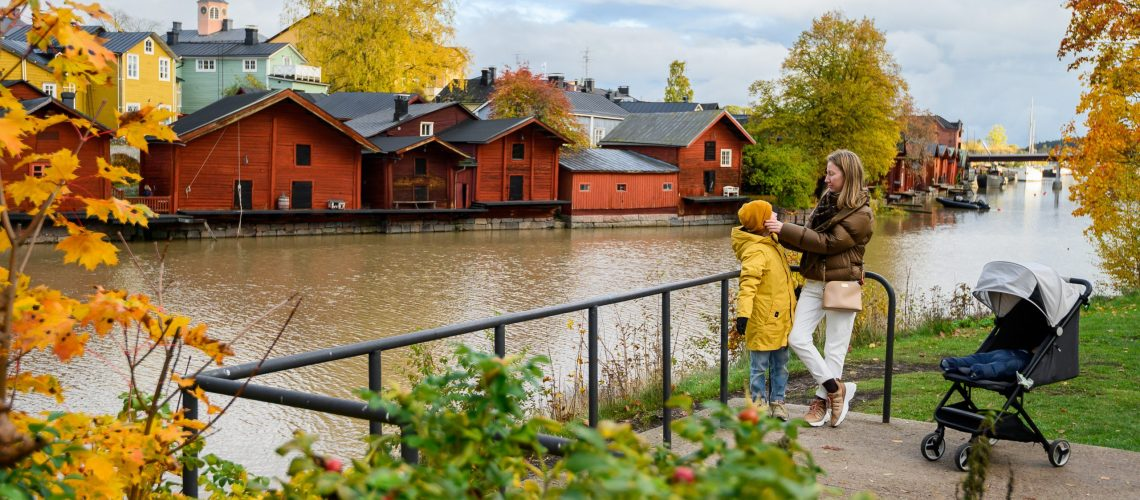 10.10.2019 Porvoo, Finland, Mother and son on the river embankment. On the background of old red houses barns.
